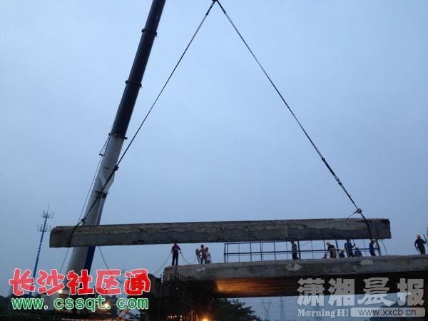 吊车正将扬子路大桥数十吨重一片的钢筋混凝土箱梁卸下.-长沙跨京